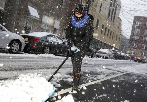 Noemi Napoles helps to shovel snow in front of her house in West New York, N.J., Wednesday, March 7, 2018.