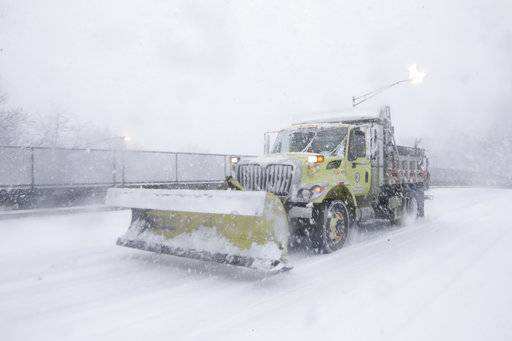 A snow plow rolls over a snow-covered road during a snowstorm, Wednesday, March 7, 2018, in Morristown, N.J.