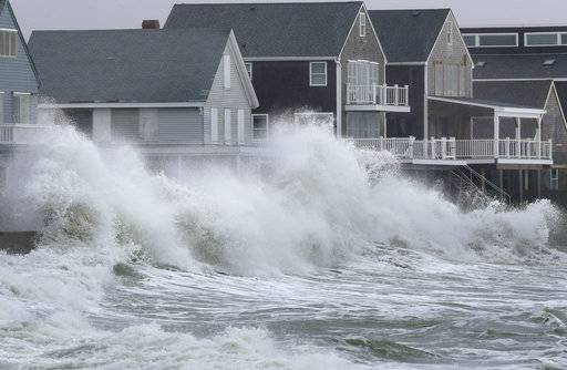 Waves crash against houses Wednesday, March 7, 2018, in Scituate, Mass. Utilities are racing to restore power to thousands of customers in the Northeast still without electricity after last week's storm as another one threatens the hard-hit area with heavy, wet snow, high winds, and more outages.