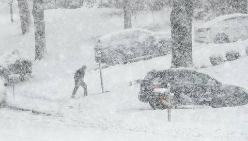A man walks back from his mailbox during a winter storm, Wednesday, March 7, 2018, in Springfield, Pa. The second big, blustery storm to hit the Northeast in less than a week brought wet, heavy snow to a corner of the country where tens of thousands of people were still waiting for the power to come back on from the previous bout.