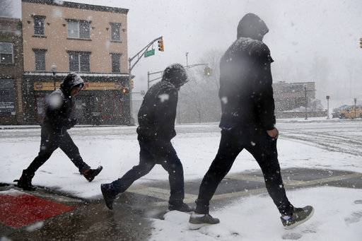 People walk on a snow-covered intersection during a snowstorm, Wednesday, March 7, 2018, in Morristown, N.J.