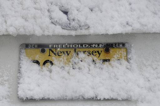 A vehicle's license plate is partially covered by snow during a snowstorm, Wednesday, March 7, 2018, in Morristown, N.J.