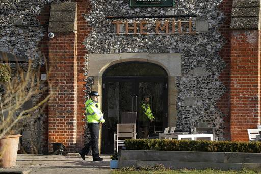 "A police community support officer stands inside a cordon outside The Mill pub in Salisbury, England, Wednesday, March 7, 2018, near to where former Russian double agent Sergei Skripal was found critically ill. Britain's counterterrorism police took over an investigation Tuesday into the mysterious collapse of the former spy and his daughter, now fighting for their lives. The government pledged a ""robust"" response if suspicions of Russian state involvement are proven. Skripal and his daughter are in a critical condition after collapsing in the English city of Salisbury on Sunday."