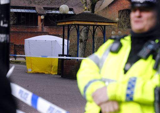 "Police officer secures the area as a police tent covers the the spot in Salisbury, England, Tuesday, March 6, 2018, where former Russian spy double agent Sergei Skripal and his companion were found critically ill Sunday following exposure to an ""unknown substance"".  66-year old Skripal, and unidentified woman companion are being treated in hospital, after they were found unconscious on the park bench."