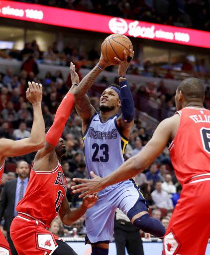 Memphis Grizzlies' Ben McLemore, center, shoots between Chicago Bulls' David Nwaba, left, and Cristiano Felicio, right, during the first half of an NBA basketball game Wednesday, March 7, 2018, in Chicago.