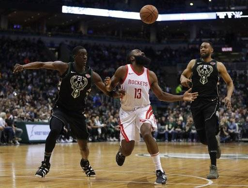 Houston Rockets' James Harden loses the ball between Milwaukee Bucks' Tony Snell and Jabari Parker during the first half of an NBA basketball game Wednesday, March 7, 2018, in Milwaukee.