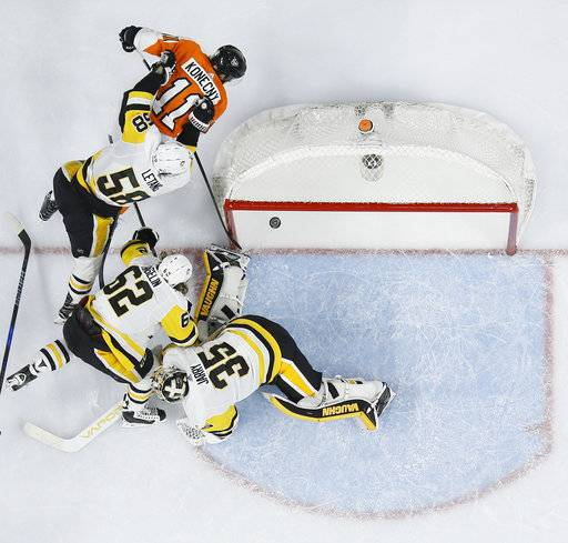Philadelphia Flyers' Travis Konecny (11) scores a goal past Pittsburgh Penguins' Kris Letang (58), Carl Hagelin (62) and Tristan Jarry (35) during the second period of an NHL hockey game, Wednesday, March 7, 2018, in Philadelphia.