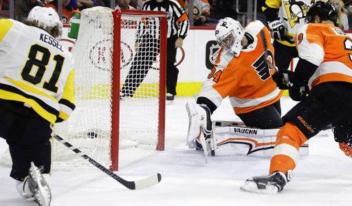 Pittsburgh Penguins' Phil Kessel, left, scores a goal past Philadelphia Flyers' Petr Mrazek, center, and Radko Gudas during the first period of an NHL hockey game, Wednesday, March 7, 2018, in Philadelphia.