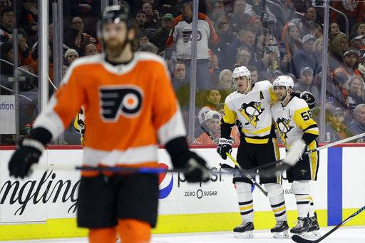 Pittsburgh Penguins' Evgeni Malkin, center, and Kris Letang celebrate past Philadelphia Flyers' Sean Couturier, left, after a goal by Malkin during the third period of an NHL hockey game, Wednesday, March 7, 2018, in Philadelphia. Pittsburgh won 5-2.