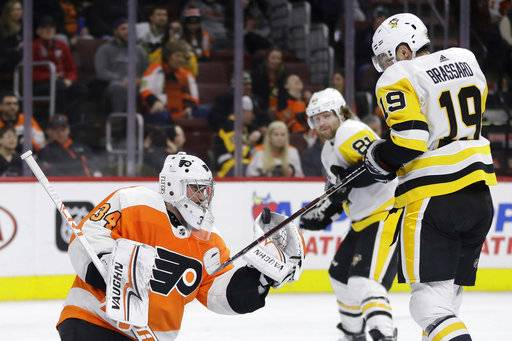 Philadelphia Flyers' Petr Mrazek (34) blocks a shot as Pittsburgh Penguins' Derick Brassard (19) tries to deflect during the third period of an NHL hockey game, Wednesday, March 7, 2018, in Philadelphia. Pittsburgh won 5-2.