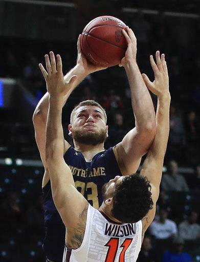Notre Dame forward Martinas Geben (23) shoots against Virginia Tech guard Devin Wilson (11) during the first half of an NCAA college basketball game in the second round of the Atlantic Coast Conference men's tournament Wednesday, March 7, 2018, in New York.