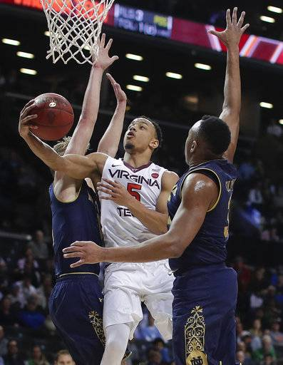 Virginia Tech guard Justin Robinson (5) shoots between Notre Dame guard Rex Pflueger, left, and forward Bonzie Colson during the second half of an NCAA college basketball game in the second round of the Atlantic Coast Conference men's tournament Wednesday, March 7, 2018, in New York. Notre Dame won 71-65.