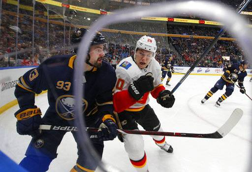 Buffalo Sabres defenseman Victor Antipin (93) is checked by Calgary Flames forward Curtis Lazar (20) during the first period of an NHL hockey game, Wednesday, March. 7, 2018, in Buffalo, N.Y.