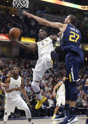 Indiana Pacers' Victor Oladipo is fouled by Utah Jazz's Rudy Gobert during the first half of an NBA basketball game Wednesday, March 7, 2018, in Indianapolis.