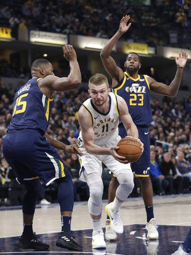 Indiana Pacers' Domantas Sabonis goes to the basket between Utah Jazz's Derrick Favors, left, and Royce O'Neale during the first half of an NBA basketball game Wednesday, March 7, 2018, in Indianapolis.