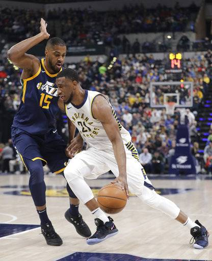 Indiana Pacers' Thaddeus Young goes to the basket as Utah Jazz's Derrick Favors defends during the first half of an NBA basketball game Wednesday, March 7, 2018, in Indianapolis.