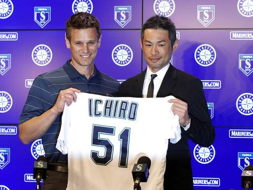 Seattle Mariners' Ichiro Suzuki, right, holds up his jersey with Mariners general manager Jerry Dipoto during a news conference at the teams' spring training baseball complex Wednesday, March 7, 2018, in Peoria, Ariz. Suzuki signed a one-year deal with the team.