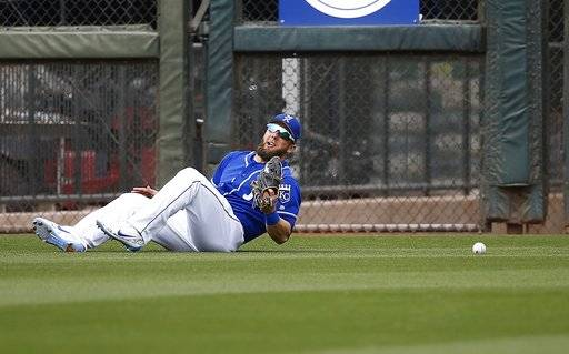 Kansas City Royals left fielder Alex Gordon is unable to come up with a ball hit by Milwaukee Brewers' Domingo Santana during the fourth inning of a spring training baseball game Wednesday, March 7, 2018, in Surprise, Ariz.