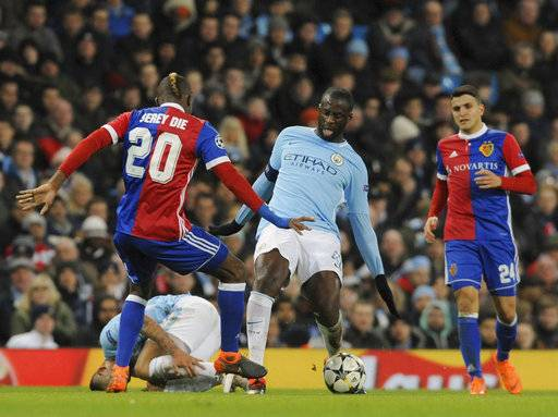 Manchester City's Yaya Toure, center, challenges for the ball with Basel's Geoffroy Serey Die, left, during the Champions League, round of 16, second leg soccer match between Manchester City and Basel at the Etihad Stadium in Manchester, England, Wednesday, March 7, 2018.
