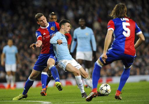 Basel's Fabian Frei, left, challenges for the ball with Manchester City's Phil Foden, center, during the Champions League, round of 16, second leg soccer match between Manchester City and Basel at the Etihad Stadium in Manchester, England, Wednesday, March 7, 2018.