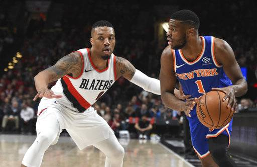 New York Knicks guard Emmanuel Mudiay tries togged past Portland Trail Blazers guard Damian Lillard during the first half of an NBA basketball game in Portland, Ore., Tuesday, March 6, 2018.