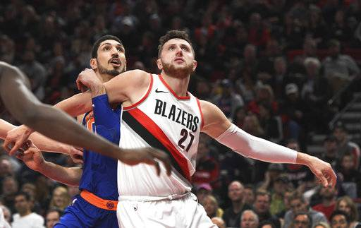 New York Knicks center Enes Kanter and Portland Trail Blazers center Jusuf Nurkic battle for position for a rebound during the first half of an NBA basketball game in Portland, Ore., Tuesday, March 6, 2018.