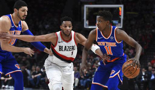 New York Knicks guard Frank Ntilikina tries to get past Portland Trail Blazers forward Evan Turner as Knicks center Enes Kanter watches during the first half of an NBA basketball game in Portland, Ore., Tuesday, March 6, 2018.