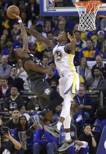 Golden State Warriors forward Jordan Bell, right, defends a shot by Brooklyn Nets guard Caris LeVert during the first half of an NBA basketball game in Oakland, Calif., Tuesday, March 6, 2018.