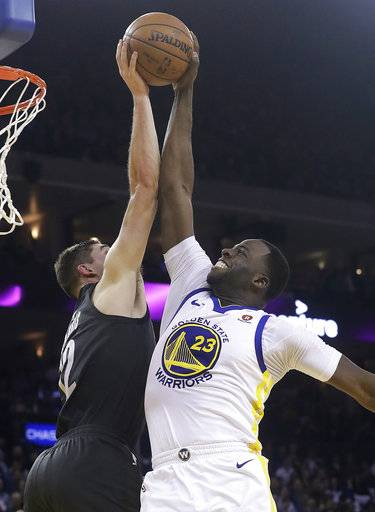 Brooklyn Nets forward Joe Harris, left, blocks a shot by Golden State Warriors forward Draymond Green (23) during the first half of an NBA basketball game in Oakland, Calif., Tuesday, March 6, 2018.