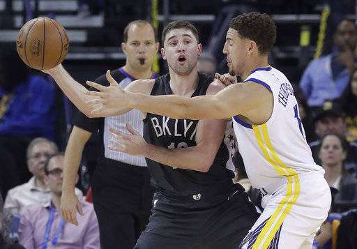 Brooklyn Nets forward Joe Harris, left, passes as Golden State Warriors guard Klay Thompson defends during the first half of an NBA basketball game in Oakland, Calif., Tuesday, March 6, 2018.