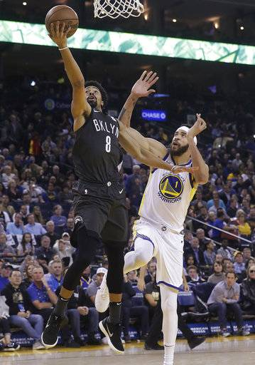 Brooklyn Nets guard Spencer Dinwiddie (8) shoots next to Golden State Warriors center JaVale McGee (1) during the second half of an NBA basketball game in Oakland, Calif., Tuesday, March 6, 2018.