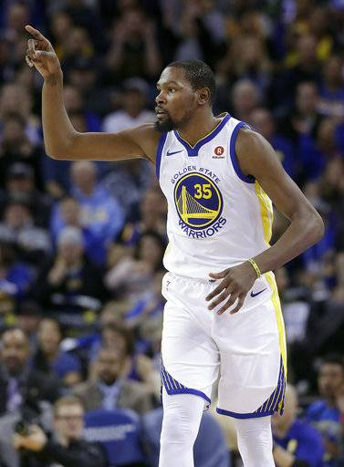 Golden State Warriors forward Kevin Durant gestures after scoring against the Brooklyn Nets during the second half of an NBA basketball game in Oakland, Calif., Tuesday, March 6, 2018.