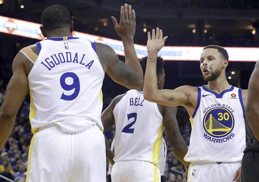 Golden State Warriors forward Andre Iguodala (9) and guard Stephen Curry (30) celebrate during the first half of the team's NBA basketball game against the Brooklyn Nets in Oakland, Calif., Tuesday, March 6, 2018.