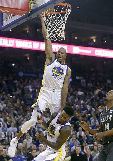 Golden State Warriors forward Andre Iguodala (9) shoots over teammate Jordan Bell (2) and in front of Brooklyn Nets forward Dante Cunningham (44) during the first half of an NBA basketball game in Oakland, Calif., Tuesday, March 6, 2018.