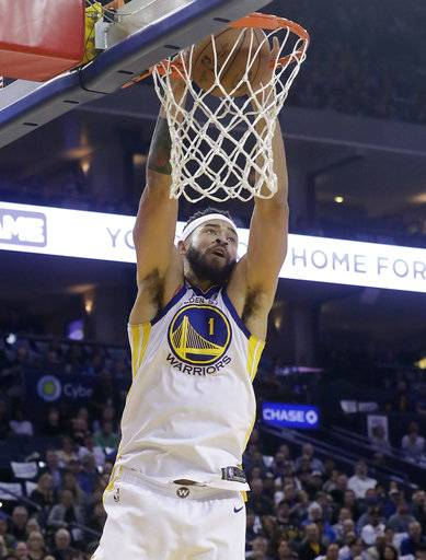 Golden State Warriors center JaVale McGee dunks against the Brooklyn Nets during the first half of an NBA basketball game in Oakland, Calif., Tuesday, March 6, 2018.