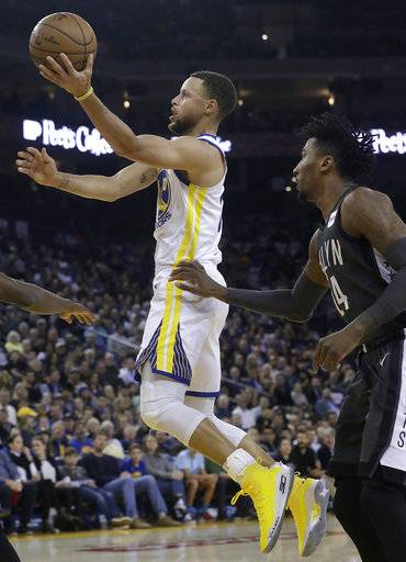 Golden State Warriors guard Stephen Curry, left, shoots in front of Brooklyn Nets forward Rondae Hollis-Jefferson during the first half of an NBA basketball game in Oakland, Calif., Tuesday, March 6, 2018.