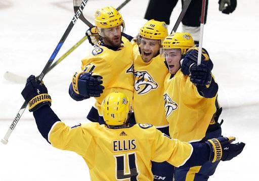 Nashville Predators right wing Ryan Hartman (38) celebrates with Ryan Ellis (4), Austin Watson (51) and Colton Sissons (10) after Hartman scored a goal against the Dallas Stars in the third period of an NHL hockey game Tuesday, March 6, 2018, in Nashville, Tenn.