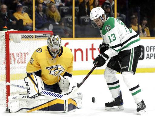 Dallas Stars center Mattias Janmark (13), of Sweden, reaches for the rebound after Nashville Predators goalie Pekka Rinne (35), of Finland, blocked a shot in the first period of an NHL hockey game Tuesday, March 6, 2018, in Nashville, Tenn.