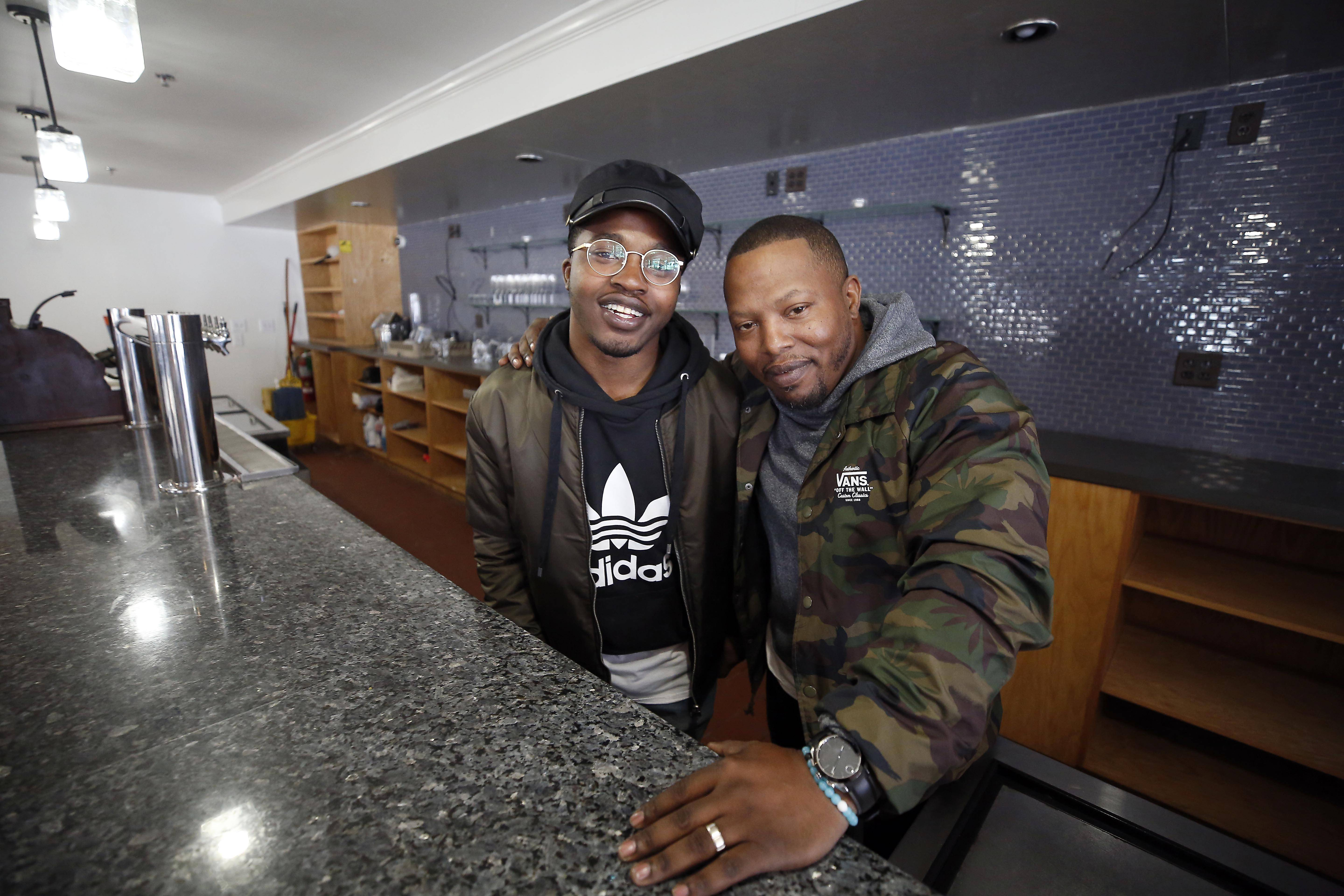 Tyrrel Tomlin, right, with son Cameron, in his new Elgin Area Taproom, to be located inside the new Dream Hall on South Grove Avenue in downtown Elgin.