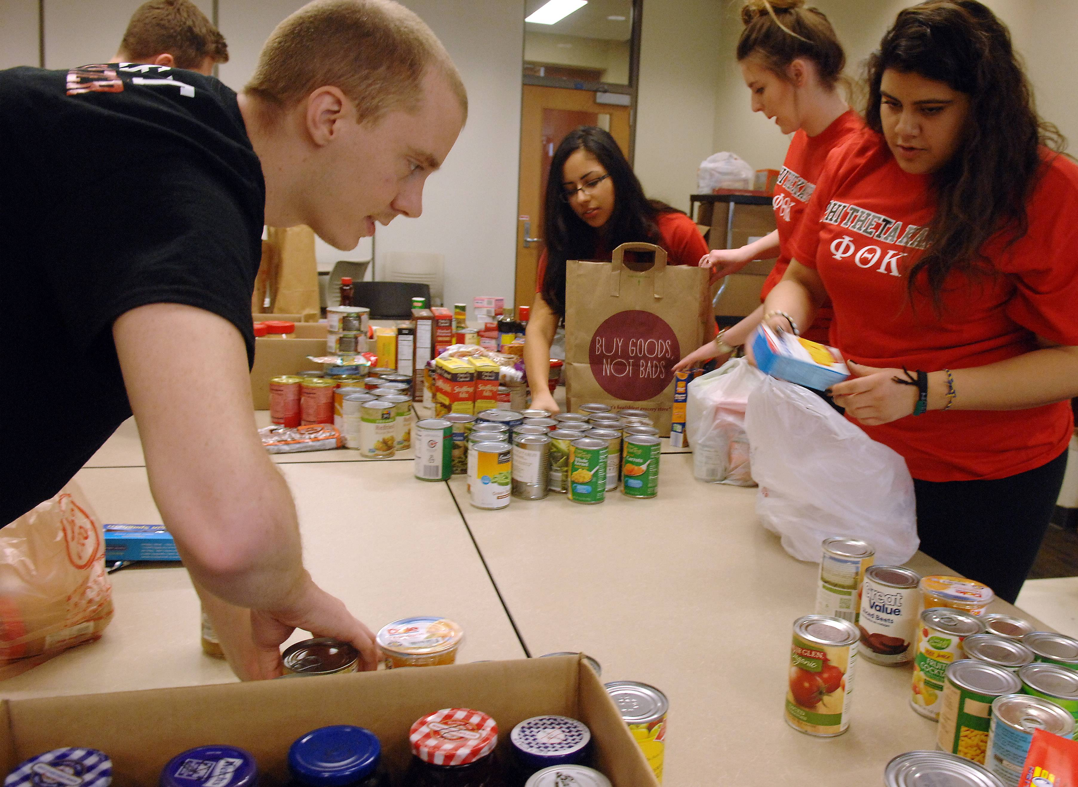 Members of the Elgin Community College branch of Phi Theta Kappa sort food as they help an on-campus pantry for students in need.