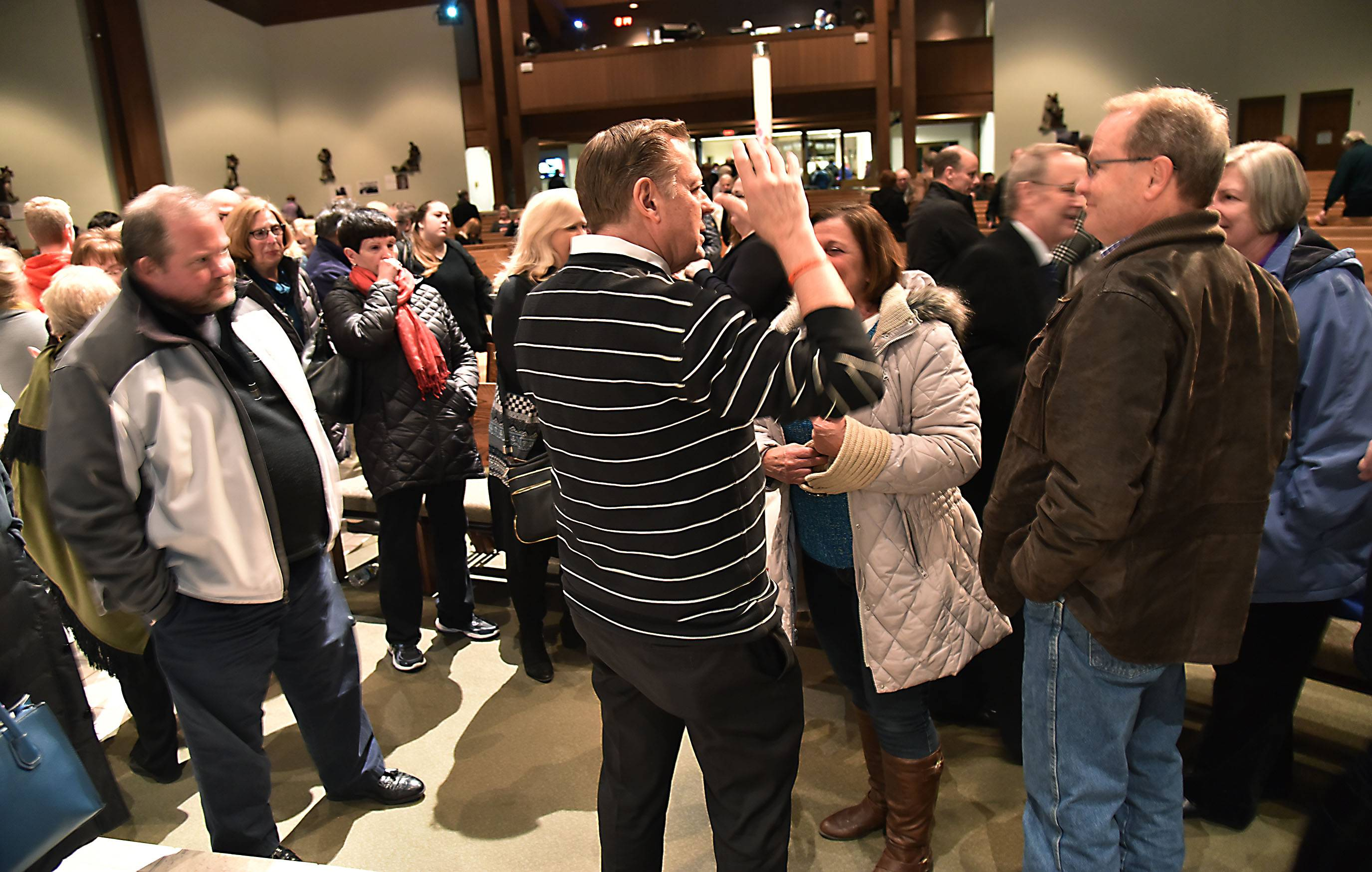 Chicago activist priest Michael Pfleger is surrounded by parishioners Thursday evening after he spoke at Holy Family Catholic Community in Inverness. Pfleger, pastor of the Faith Community of St. Sabina on the city's south side, discussed inner city violence and other issues.