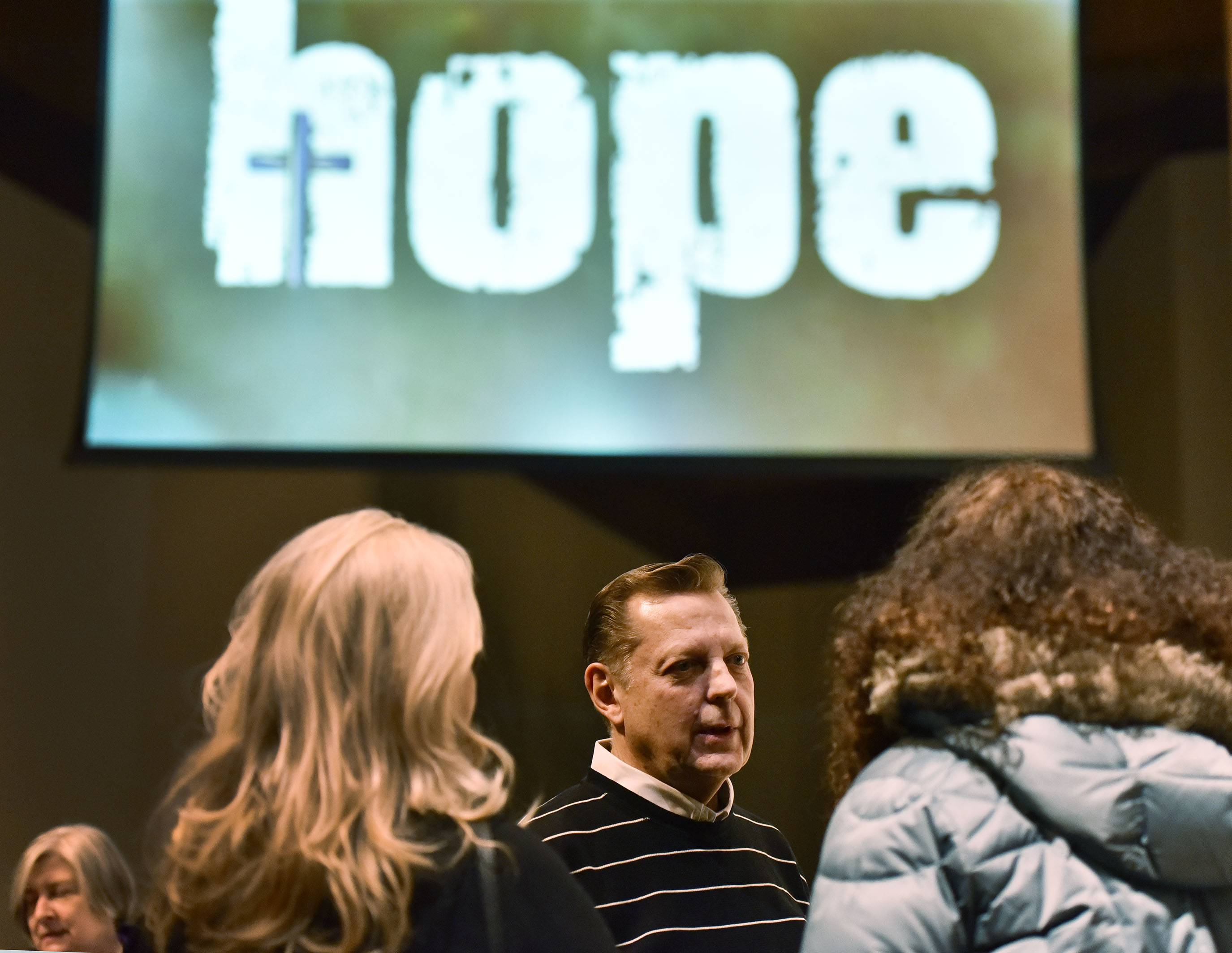 Chicago activist priest Michael Pfleger talks with parishioners after a speech at Holy Family Catholic Community in Inverness Thursday night.