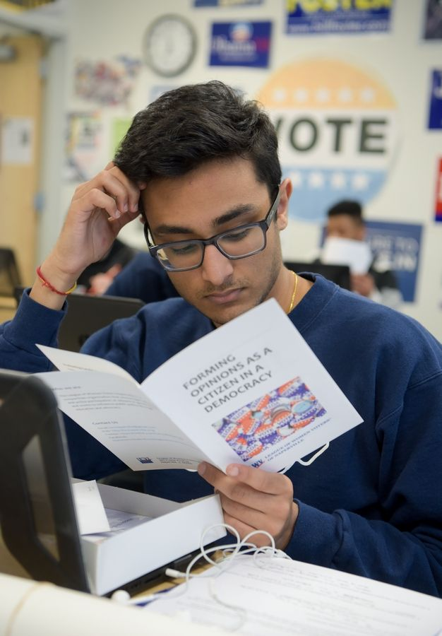 Rohan Agarwal, 18, of Naperville, reads though a voter information booklet Thursday from the League of Women Voters of Naperville.