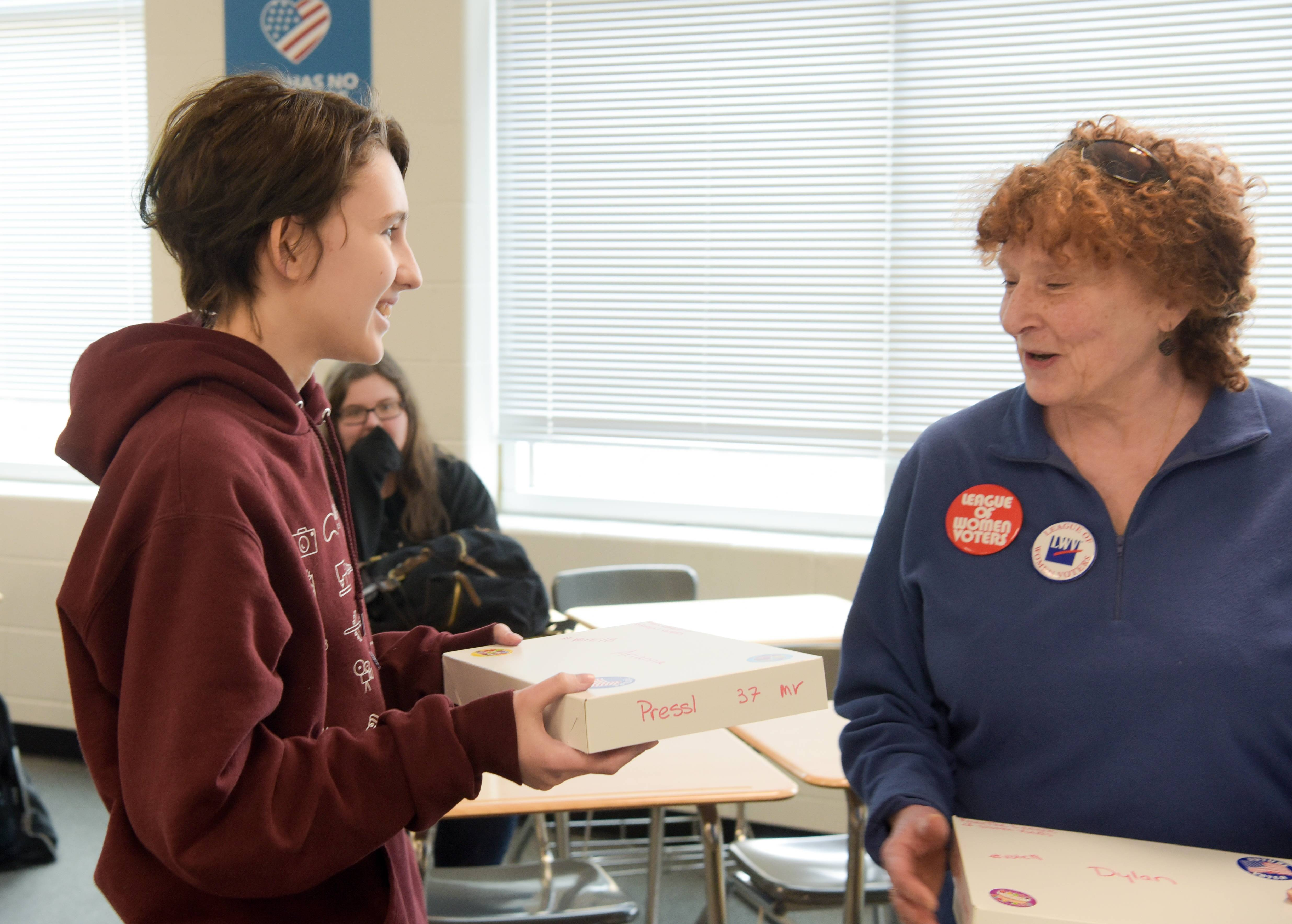 Metea Valley High School student Arianna Presso, 18, of Naperville, talks with Susan Greenwood of the League of Women Voters of Naperville as Greenwood gives her a Birthday Box of nonpartisan voter information.