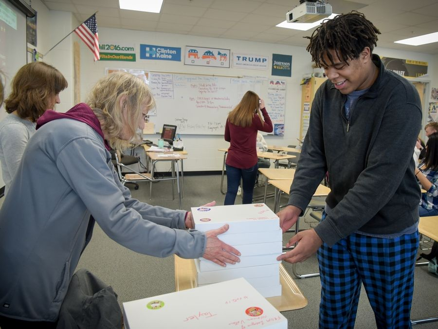 Annette Smith of The League of Women Voters of Naperville gives Grant Chandler, 18, of Naperville, his Birthday Box of nonpartisan voter information Thursday during Susan Fuhrer's American Government class at Metea Valley High School.