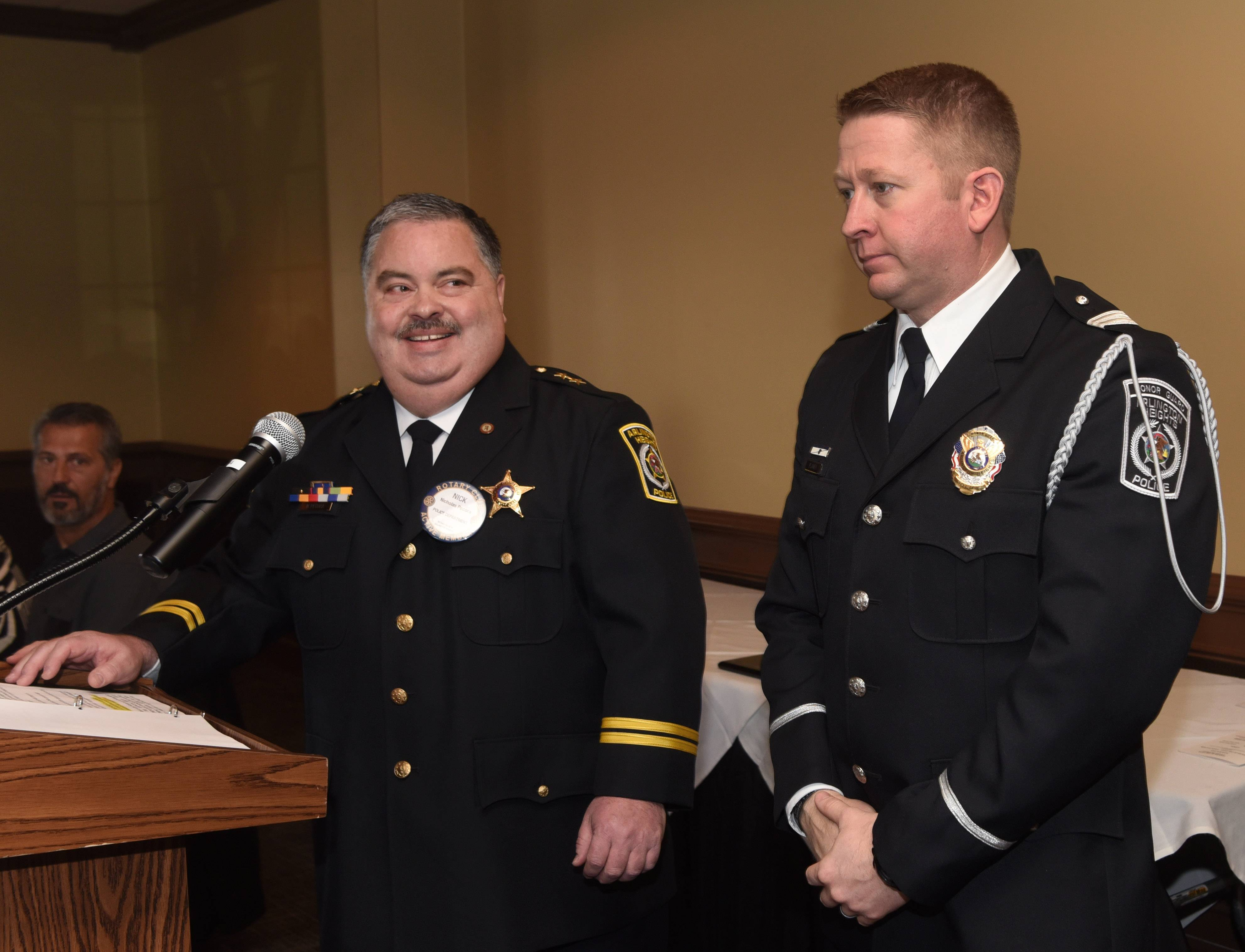 Arlington Heights Deputy Police Chief Nick Pecora, left, said Adam Plawer put his safety at risk when he rescued an unconscious driver from a burning vehicle last summer. Plawer on Thursday won the department's L.W. Calderwood Officer of the Year Award.