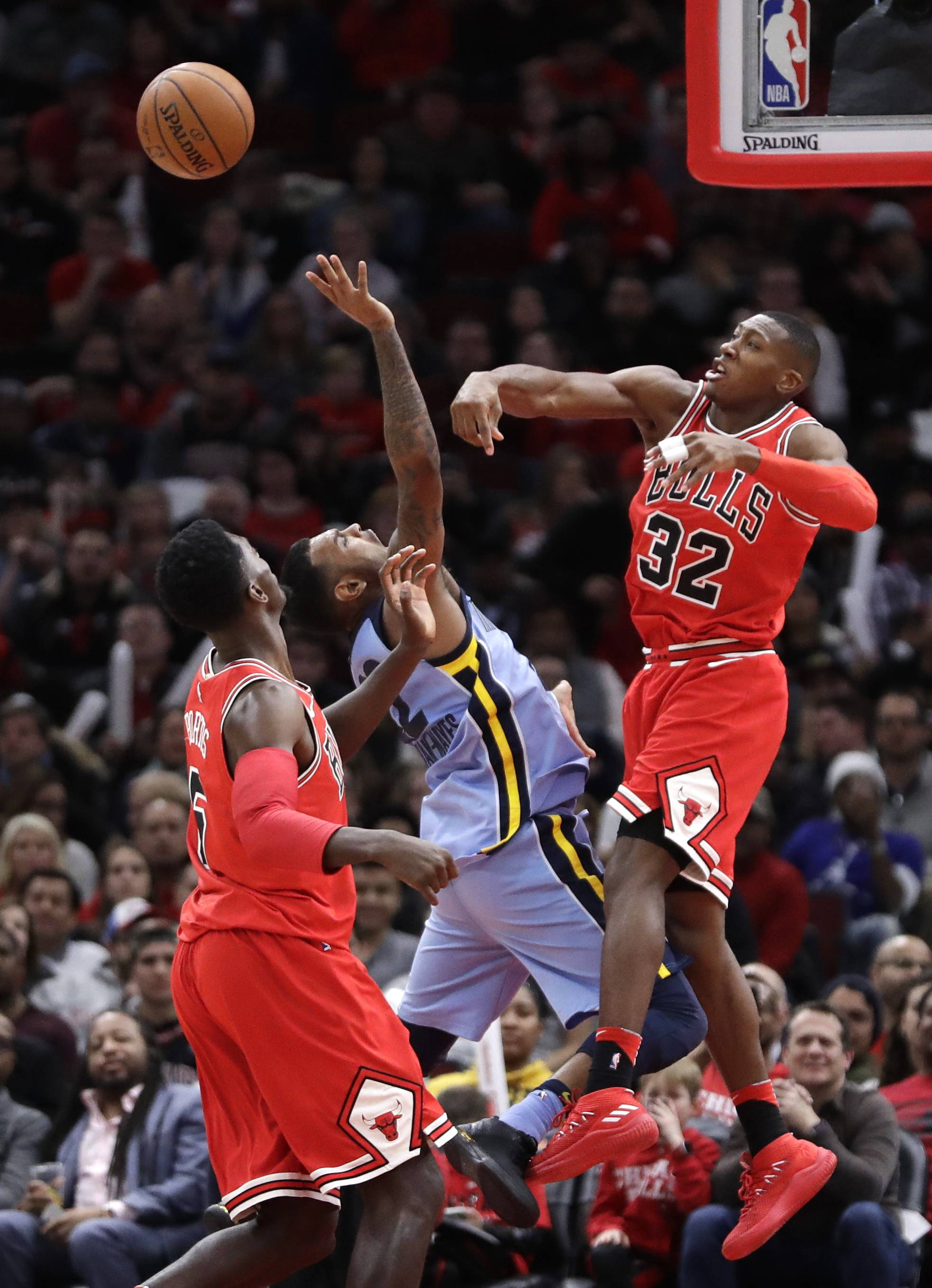 Chicago Bulls' Kris Dunn (32) blocks the shot of Xavier Rathan-Mayes as Bobby Portis watches during the second half of an NBA basketball game against the Memphis Grizzlies Wednesday, March 7, 2018, in Chicago