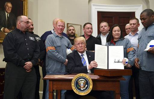 President Donald Trump holds up a proclamation on steel imports during an event in the Roosevelt at the White House in Washington, Thursday, March 8, 2018. He also signed one for aluminum imports.