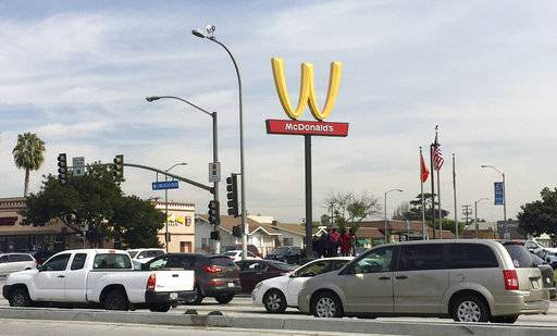 "Motorists make their way past a McDonald's restaurant with a flipped Golden Arches sign Thursday, March 8, 2018, in Lynwood, Calif. McDonald's has temporarily flipped its famous Golden Arches to look like a ""W,"" a move it says it made to recognize International Women's Day."