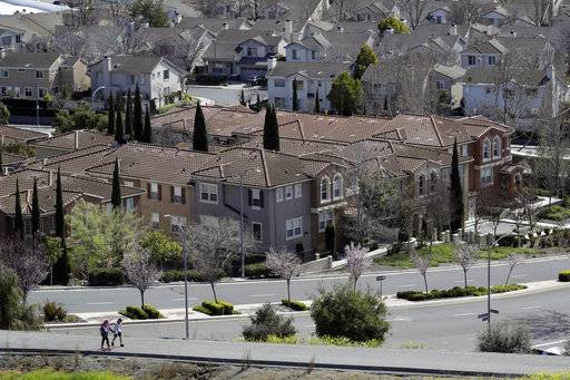 In this Tuesday, March 6, 2018, photo people walk along a path in front of a row of homes in San Jose, Calif. NerdWallet calculated affordability for 173 metropolitan areas by comparing the median annual household income and the monthly principal-and-interest payment for a median-priced single-family home and found that the least affordable homes are in the San Jose.
